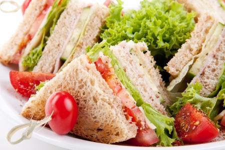 turkey bacon: fresco club sandwich gustosi con prosciutto formaggio lattuga e pane tostato isolato su sfondo bianco