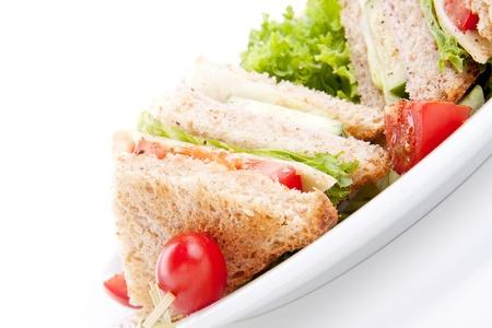sandwich de pollo: Club s�ndwich fresco sabroso con el jam�n lechuga queso y pan tostado aislados en fondo blanco