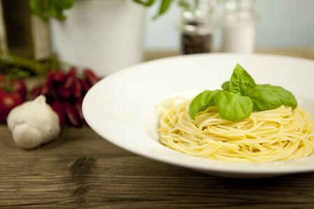 tasty fresh pasta with garlic and basil on wooden table photo