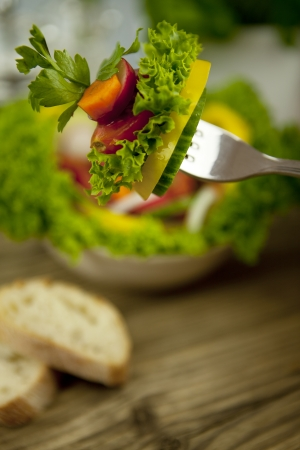 garden stuff: fresh tasty healthy mixed salad and bread on wooden table