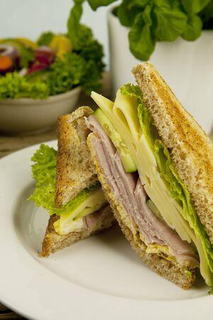 Club sándwich fresco sabroso con queso y jamón en la mesa de madera Foto de archivo