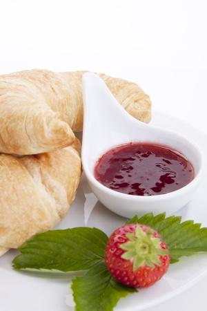 deliscios fresh croissant with strawberry jam isolated on white background photo