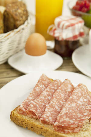 tasty breakfast with salami toast on wooden background photo