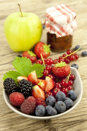 mixed fresh berries for dessert on wooden background in summer photo