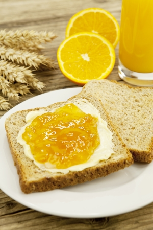 tasty breackfast with toast and marmelade on wooden background photo