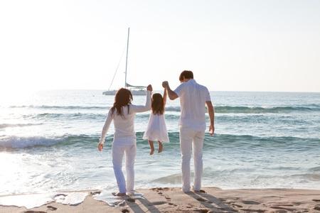 gelukkig jong gezin met dochter op strand in de zomer levensstijl Stockfoto