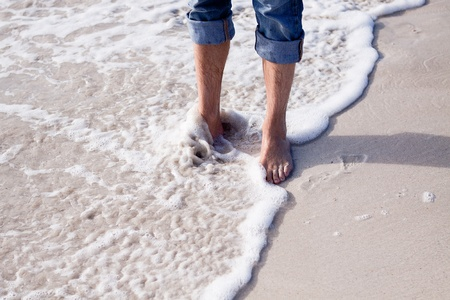 barefoot in sand and water on beach  in summer holidays relaxing photo