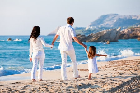 glückliche junge Familie mit Tochter am Strand im Sommer Lifestyle