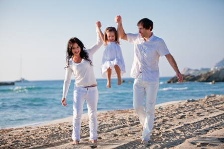 happy young family with daughter on beach in summer lifestyle photo