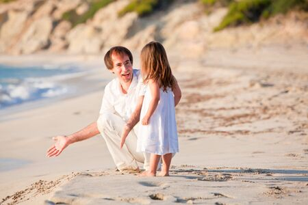 happy family father and daughter on beach having fun summer vacation photo