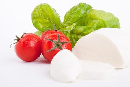 leckere Tomaten Mozarella-Salat mit Basilikum auf weißem Hintergrund