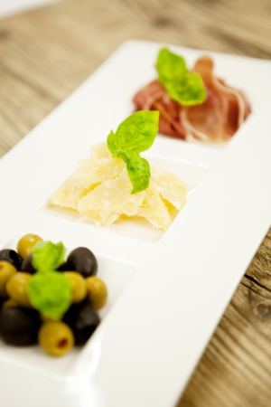 deliscious antipasti plate with parma parmesan olives on wooden background Stock Photo - 15463041