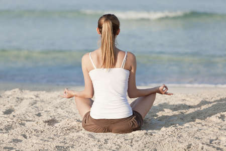 Young sporty woman doing sport yoga on the beach in the sand on the beach in the sun photo