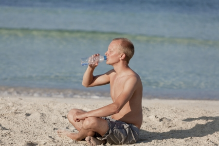 Young man boy drinking refreshing water from a bottle on the beach by the sea in summer vacation photo