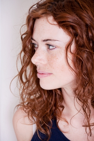 beautiful red head woman with freckled face and blue eyes Stock Photo