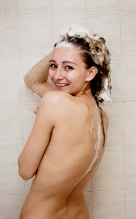 showering: young brunette woman is taking shower and washing hair