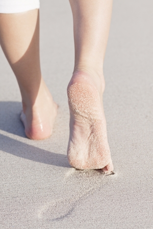 walking barefoot in the sand in summer holidays on beach photo