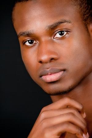 jonge Afrikaanse afro man met een donkere huid op zwarte achtergrond Stockfoto