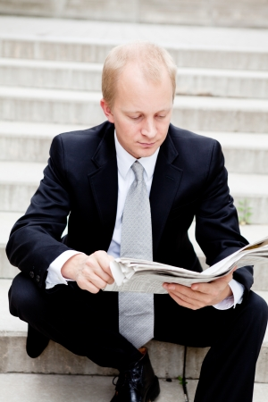 young business man is reading newspaper outdoor in summer photo