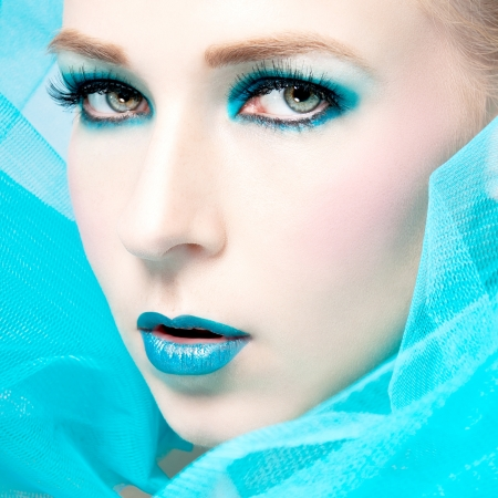 beautiful woman with extreme colorfull make up in turquoise portrait photo