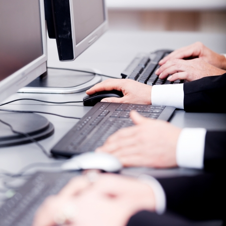 BUSY OFFICE: male hand on keyboard typing and scroll mouse on office desk Stock Photo