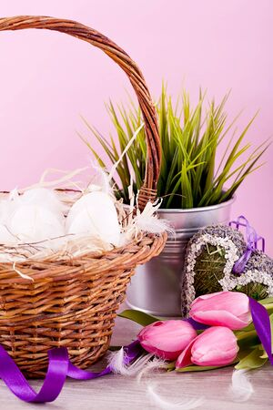 festive traditional easter egg decoration ribbon and tulips on pink background photo