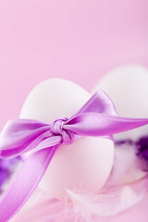 festive traditional easter egg decoration purple satin ribbon on pink  photo