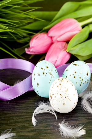traditional easter egg decoration with tulips and ribbo and feather photo