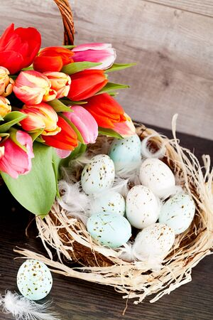 festive traditional easter egg decoration ribbon and tulips on wooden background photo