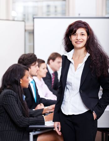 professional successful smiling business woman in office with team in background Stock Photo - 17449272