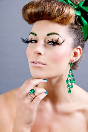 brunette woman with green jewelery and accssesoires on grey background photo