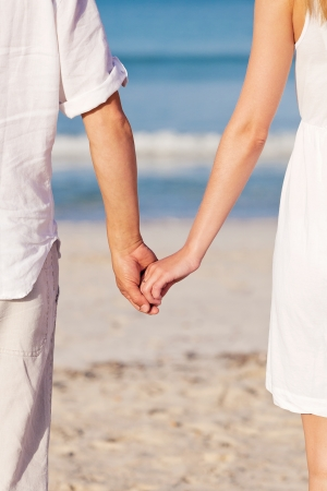 couple in love hand in hand on beach in summer holiday