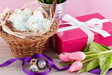 pink present with ribbon and colorful tulips festive easter decoration photo