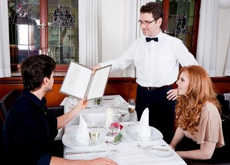 레스토랑 웨이터 남자와 여자는 카드 주문 음식을 가지고
