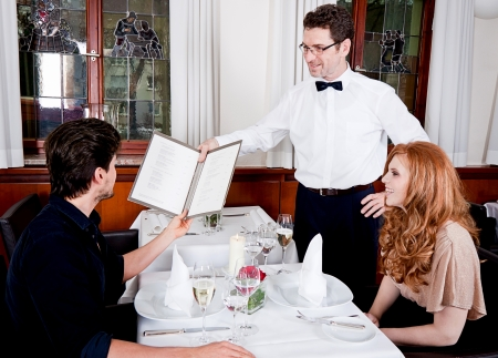 man and woman in restaurant waiter bring card and order food