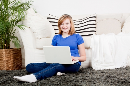 young teenager girl with laptop smilig ssitting on couch  photo
