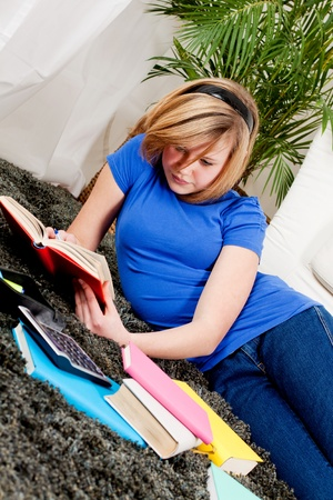 teenager girl sitting on the floor with lot of books and doing homework learning reading photo