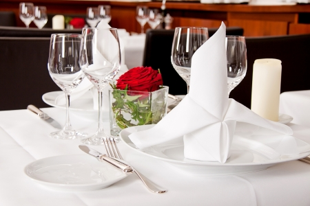 fine silver: tables in restaurant with white tablecloth and elegant dish and silverwear Stock Photo
