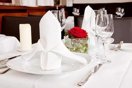 tables in restaurant with white tablecloth and elegant dish and silverwear photo
