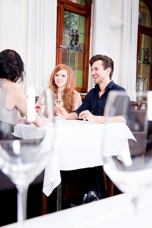 smiling happy people in restaurant drinking talking having fun  Stock Photo