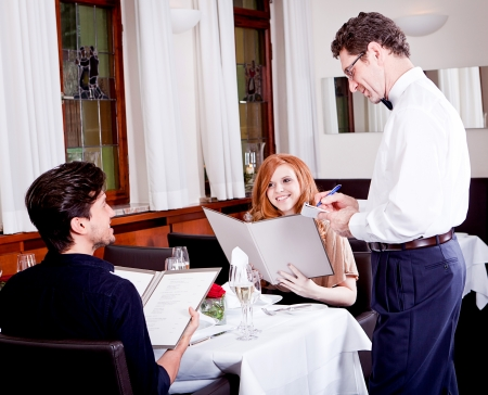 man and woman in restaurant waiter bring card and order food photo