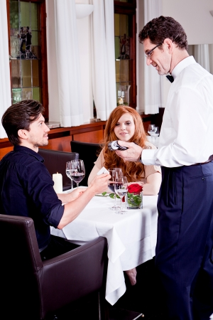 dinner in restaurant man and woman pay by credit card Фото со стока