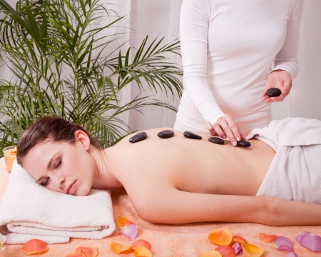 young attractive woman get hot stone massage by professional in wellness spa salon