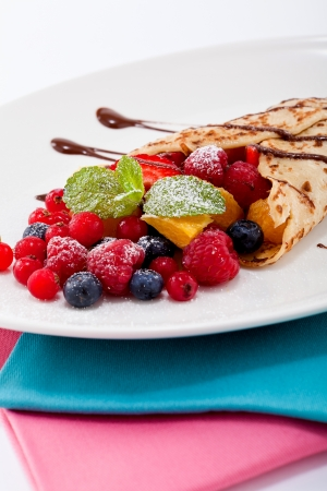 fresh tasty homemade crepe pancake with chocolate sauce fruits and berries photo