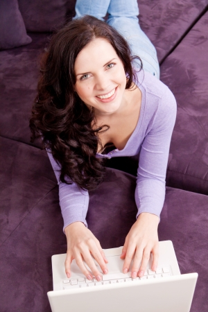 attractive young smiling woman on couch with notebook  photo