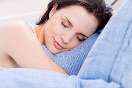 schöne junge Frau im Bett schlafen blaue Decke