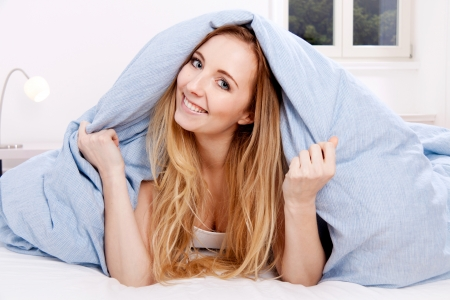 cute smiling blonde woman in the morning under blanket Stock Photo - 18937801