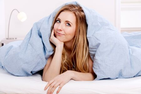 bedcover: cute smiling blonde woman in the morning under blanket Stock Photo