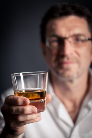 adult man holding an alcoholic drink thoughtful on black background Stock Photo