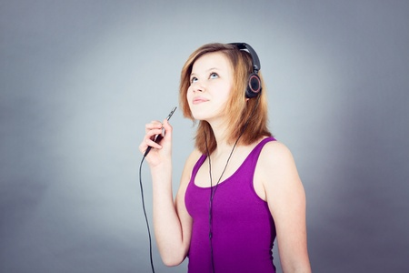 young smiling teenager girl dancing with mp3 player and earphones listening to music photo